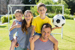 Portrait of smiling parents carrying their two children on their shoulders. In the park Royalty Free Stock Photo