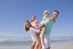 Portrait of smiling parents piggybacking children on sunny beach Royalty Free Stock Images