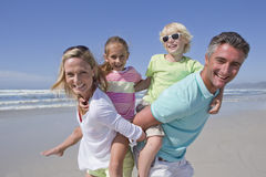Portrait of smiling parents piggybacking children on sunny beach Stock Photography
