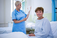 Portrait of smiling patient sitting on bed Stock Photos