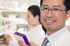 Portrait of smiling pharmacist holding prescription medication and looking at camera Stock Photo