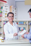 Portrait of a smiling pharmacist holding a prescription Royalty Free Stock Photos