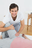 Portrait of a smiling physical therapist examining womans leg Royalty Free Stock Image