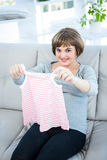 Portrait of smiling pregnant woman holding baby clothes Royalty Free Stock Photo