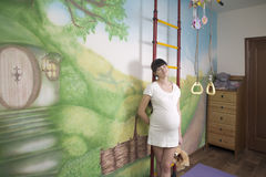 Portrait of smiling pregnant woman leaning on ladder Royalty Free Stock Images