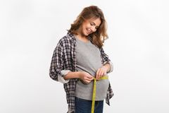 portrait of smiling pregnant woman measuring tummy with measuring tape royalty free stock photo