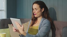 Portrait of smiling pregnant woman sitting with tablet on couch indoors. stock video footage