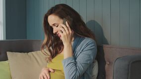 Portrait of smiling pregnant woman talking smartphone on couch at modern home. stock video