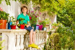 Happy boy sitting on balustrade of balcony garden stock photos