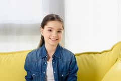 portrait of smiling preteen child looking at camera on sofa stock images