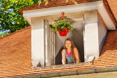 Smiling girl enjoying morning in the open window royalty free stock photography
