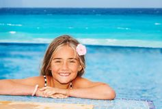 Smiling girl resting on the edge of swimming pool Royalty Free Stock Photo