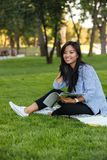 Portrait of a smiling pretty asian female student. Holding textbook while sitting on the grass at the park Royalty Free Stock Photo
