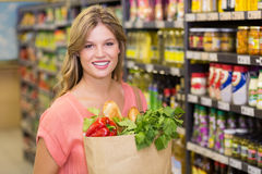 Portrait of smiling pretty blonde woman buying food products Stock Photo