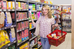 Portrait of a smiling pretty blonde woman having a product in her hands Stock Photos