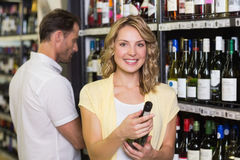 Portrait of smiling pretty blonde woman looking at wine bottle Royalty Free Stock Image
