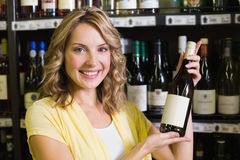 Portrait of a smiling pretty blonde woman showing a wine bottle Stock Image