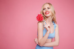 Portrait of a smiling pretty blonde woman in swimsuit posing with heart shaped lollipop and looking away Stock Photography
