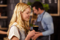 Portrait of smiling pretty customer smelling cup of coffee Royalty Free Stock Image