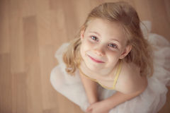 Portrait of smiling pretty diligent ballet girl sitting in white Stock Photo