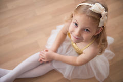 Portrait of smiling pretty diligent ballet girl sitting in white. Tutu at dance studio. View from above royalty free stock photos