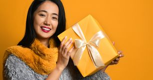 Portrait of a smiling pretty girl holding gift box isolated over yellow background stock photo