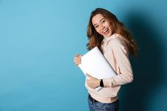 Portrait of a smiling pretty girl holding laptop computer. While standing and looking at camera isolated over blue background Stock Images