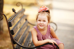 Portrait of a smiling pretty girl sitting on a park bench Stock Image