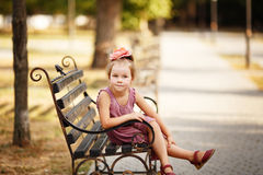 Portrait of a smiling pretty little girl sitting on a bench Stock Photos
