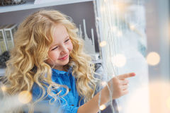 Portrait of smiling pretty little girl touches to the window Stock Photo