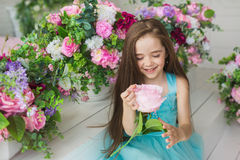 Portrait of a smiling pretty little girl in a turquoise dress holds a flower in a hands Royalty Free Stock Images