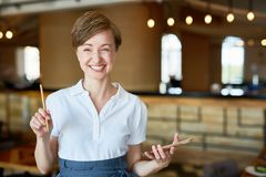 Portrait of Smiling Pretty Waitress. Waist-up portrait of cheerful pretty waitress looking at camera with charming smile while holding notepad and pencil in Stock Photo