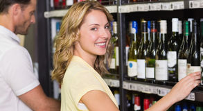 Portrait of smiling pretty woman buying a wine bottle Royalty Free Stock Image