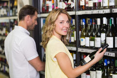 Portrait of a smiling pretty woman looking at wine bottle Stock Images