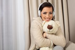 Portrait of a smiling pretty woman posing with headphones and teddy bear stock photography