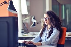 Portrait of smiling pretty young business woman in glasses sitting on workplace.  Stock Photos