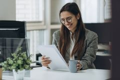 Portrait of smiling pretty young business woman in glasses sitting on workplace and working with documents stock photography