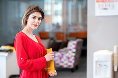 Portrait of smiling pretty young business woman holding folder a stock image