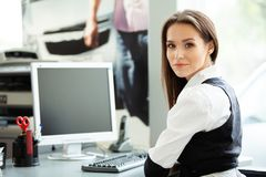 Portrait of smiling pretty young business woman sitting on workplace. royalty free stock image