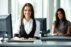 Portrait of smiling pretty young business woman sitting on workplace. stock images