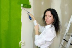 Portrait of a smiling pretty young woman is painting green interior wall with roller in a new home and pointing on her work royalty free stock photography
