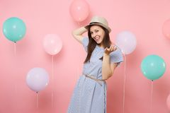 Portrait of smiling pretty young woman wearing straw summer hat and blue dress standing on pastel pink background with royalty free stock photo