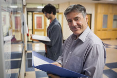 Portrait of smiling professor standing in front of notice board Royalty Free Stock Photo