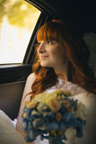 Portrait of smiling redhead bride looking out of window at car Royalty Free Stock Photos