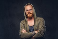 Portrait of a smiling redhead hipster with full beard and glasses dressed in hoodie and t-shirt poses with crossed arms. In a studio. Isolated on a dark stock photography