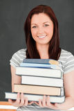 Portrait of a smiling redhead holding books Royalty Free Stock Images