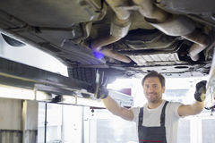 Portrait of smiling repair worker examining car in workshop Stock Photos