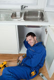Portrait of a smiling repairman fixing a sink Stock Photo