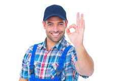 Portrait of smiling repairman gesturing okay. Portrait of smiling male repairman gesturing okay on white background Stock Images