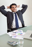 Portrait of a smiling sales person relaxing. In his office Stock Images